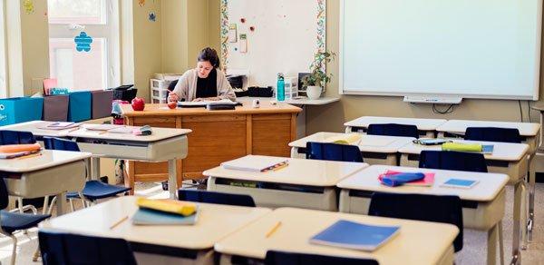 teacher-at-desk-empty-classroom-getty-600x292-1
